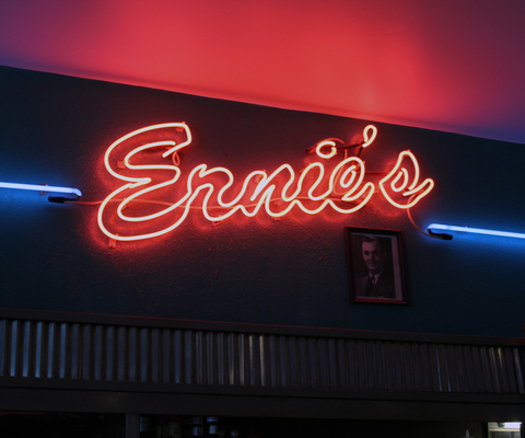 A neon sign brightly displays the Ernie's name