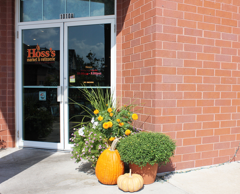 The store front of Hoss's is decorated with seasonal things like pumpkins for fall
